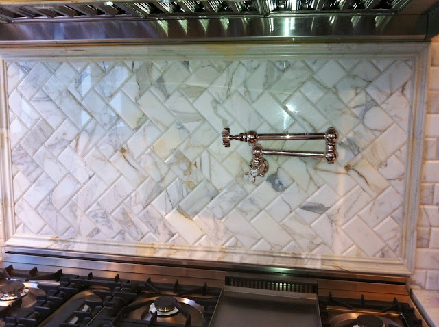 Kitchen with brushed nickel Rohl pot filler above the range is mounted on a Calacatta gold marble backsplash set in a herringbone pattern