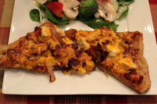 Two slices of BBQ chicken pizza on a square white plate, accompanied by a simple salad.