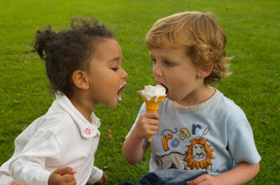 boy holding ice cream while girl waiting for her turn