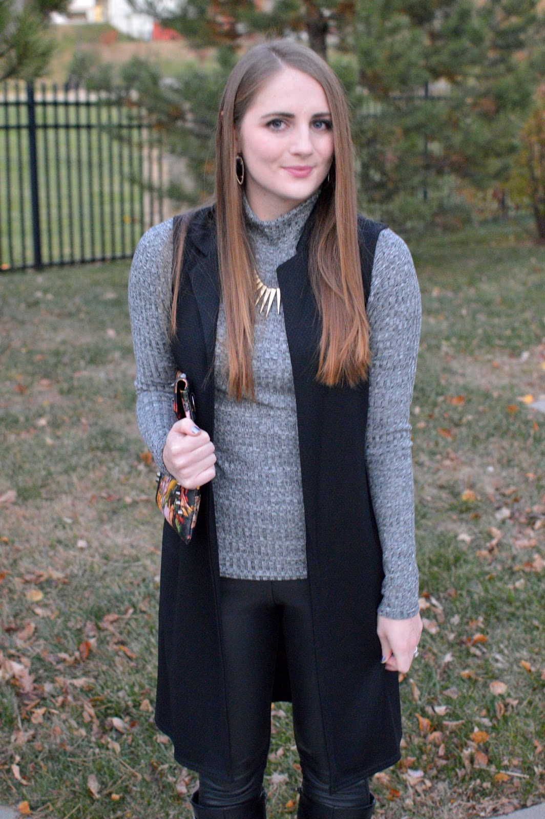 gray turtleneck with a black sleeveless trench