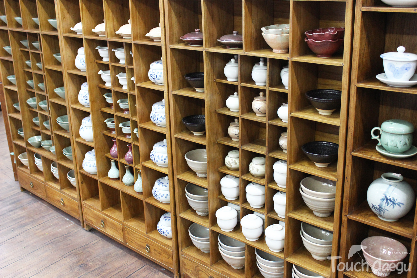 There are many tea cups on the wooden shelves