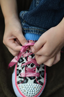 learning to tie shoes, push the lace through the thumb hole to make a second loop