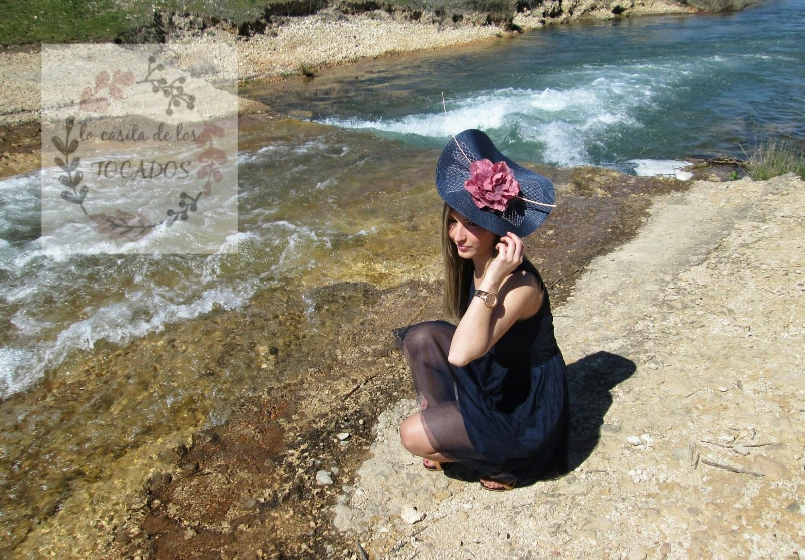 Tocado Ítaca color azul marino y rosa maquillaje, a juego con vestido en azul.