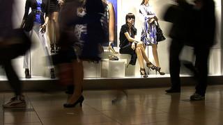 maniquí femenino, con gafas oscuras en vitrina de centro comercial viendo a la gente pasar