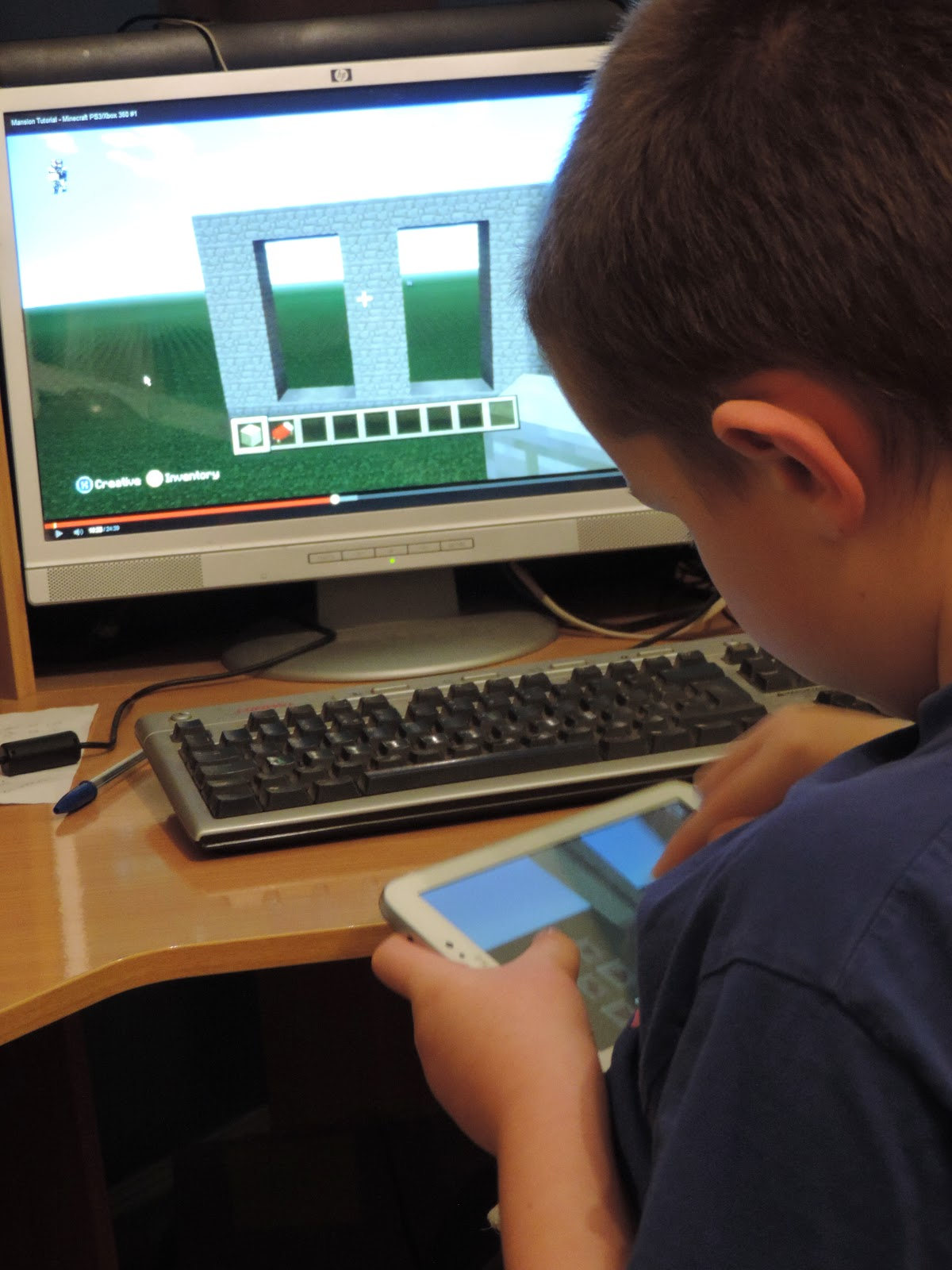 boy using tablet and pc to play minecraft