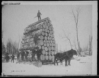 horses pulling load of logs