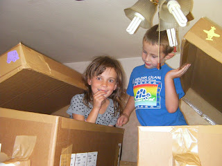 children playing in cardboard boxes
