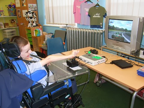Colin McDonnell playing a PS2 game with an accessible C-SID controller with joystick.