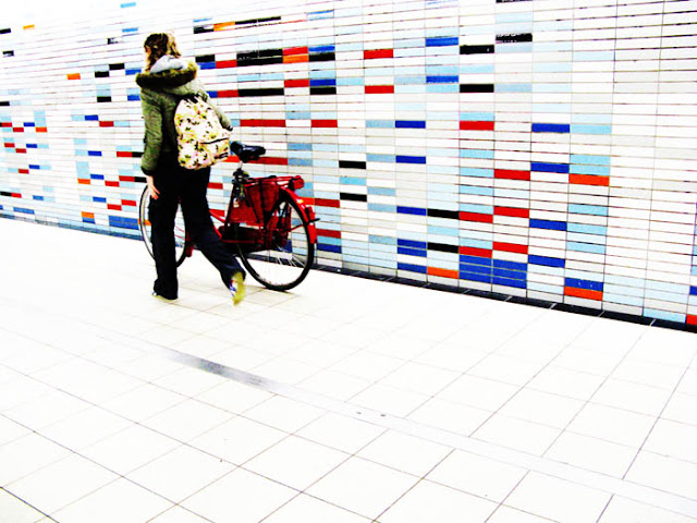 A girl walking a bike through a colorful corridor of a Dutch train station.