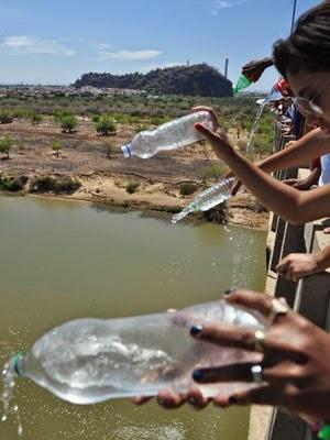Participantes jogam água no rio em crítica ao baixo nível  (Foto: Divulgação/CBHSF)