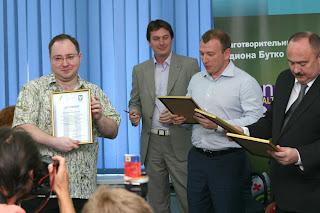глава благотворительного фонда «Благо» Родион Бутко вручает сертификат
