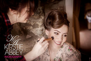 Bride wearing designer wedding gown with sophisticated vintage hair and makeup