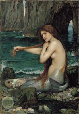mermaid primping on rocks near water