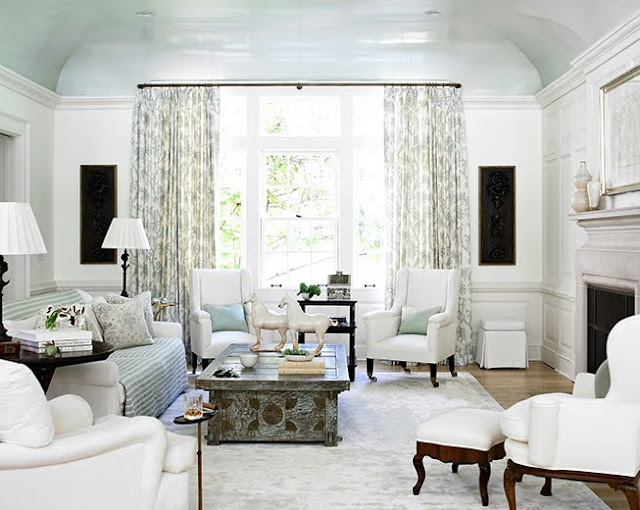 living room with glossy light blue curved ceiling, large window with patterned floor length curtains, white armchairs and a sofa with a throw over the back.