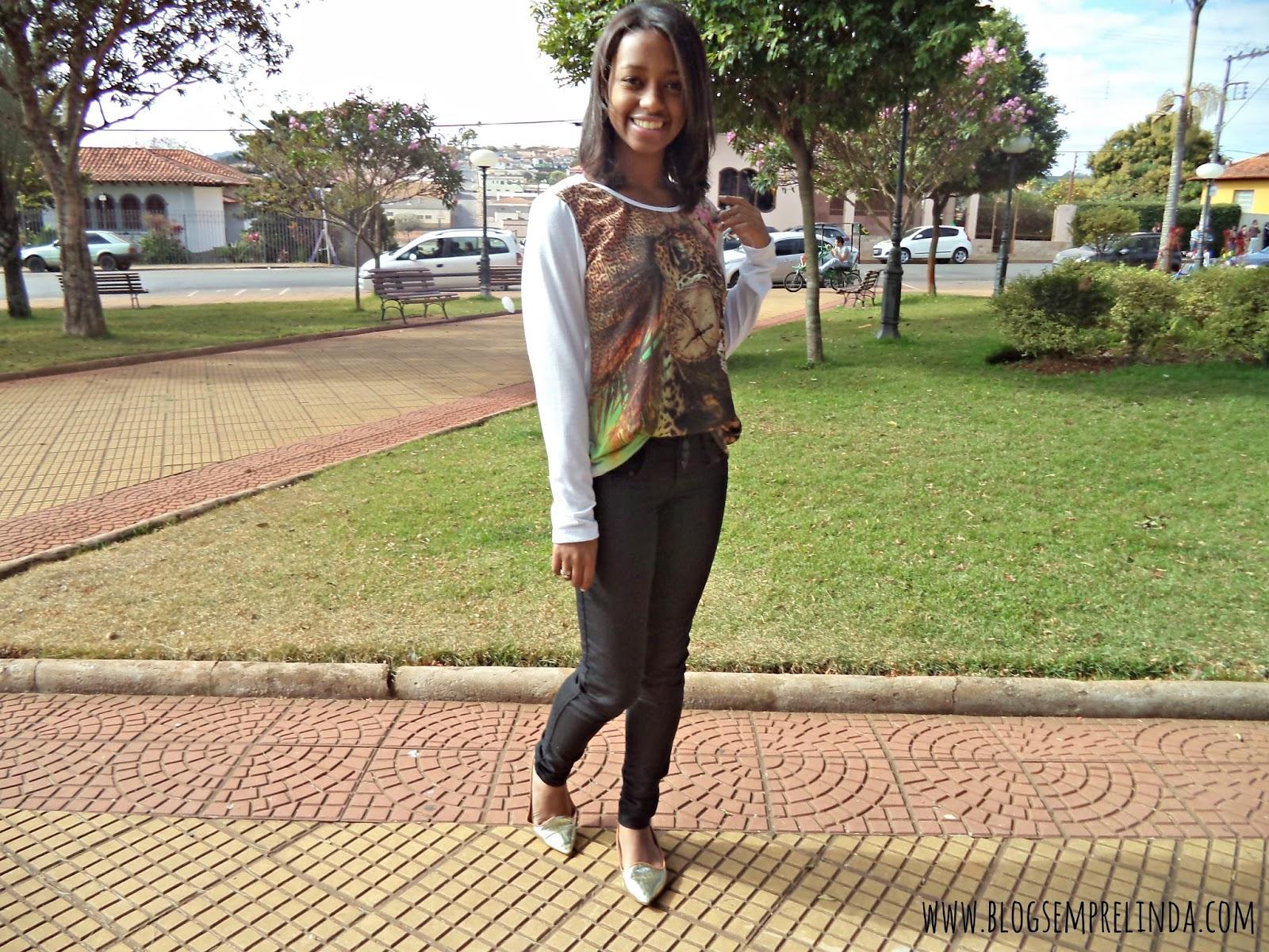 Look composto por calça preta, blusa branca com estampa animal print, com sapatilha dourada. Em uma praça verde.