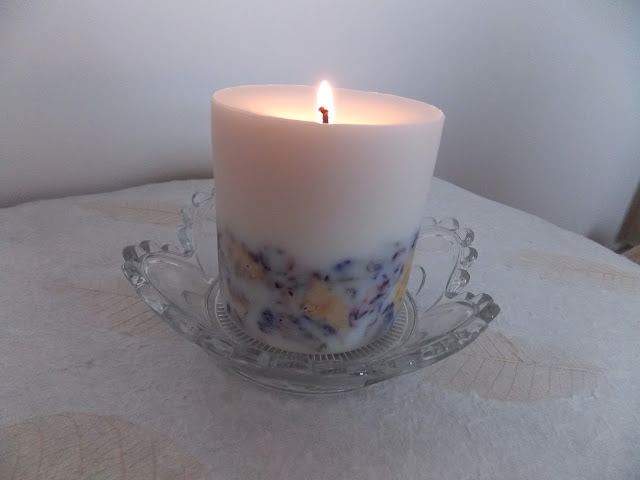 A picture of a soy candle with wild flowers visible