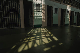 Photo of prison cells with lots of shadows.