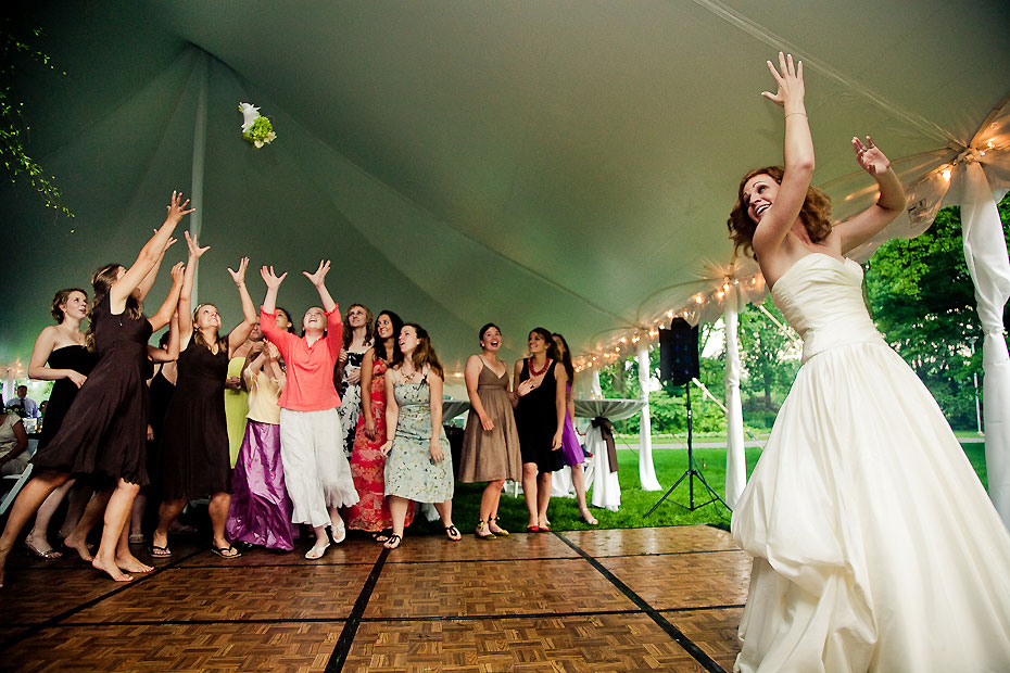 in strapless bridal gown, the bride toss the Bouquest
