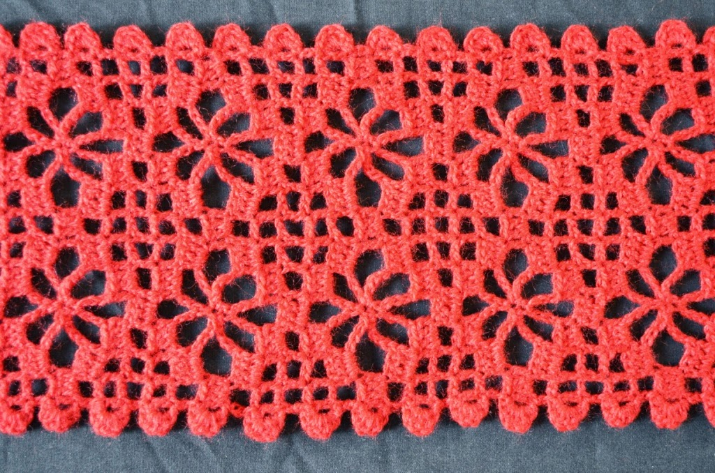 Central section of second scarf laid out horizontally and in close up: 6 x 2 spiderweb filet crochet motifs with scalloped turns at the end of each row to create a ridged edging on the top and bottom edges.