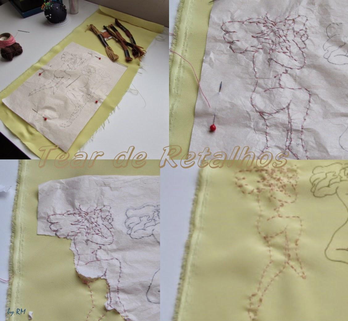Alinhavando o papel desenhado no pano a ser bordado
