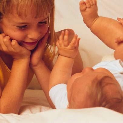 criança mais velha observando bebê com ternura
