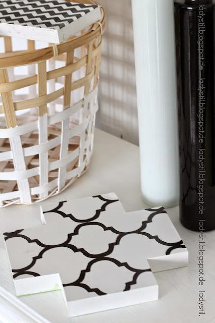 Dekoration auf weißer Kommode mit zwei Vasen eine schawrz eine weiß und einem schwarzweißen Kreuz