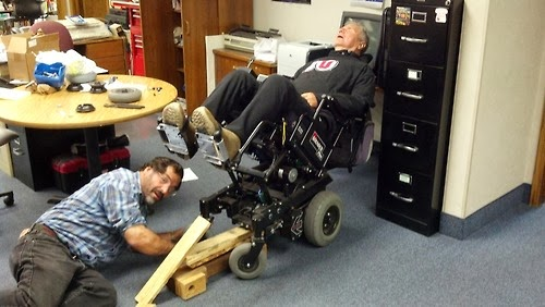 Man in reclined electric wheelchair with another man repairing the chair