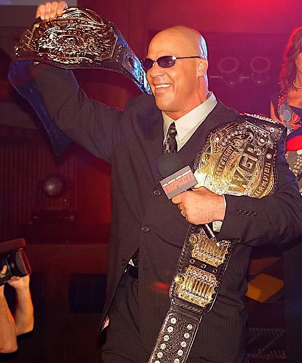 Kurt Angle holding title belts