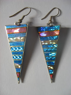 Very bright, sparkly earrings of elongated triangles (point down). Stripes of color that are perhaps glass or cloisone or lacquered beads? Top stripe is blue, then a reddish-range, then blue, then gold, then blue and a thin gold stripe, which repeats three times, then gold, blue, and a red point. Each stripe has a different texture underneath the glass so they are very shimmery.