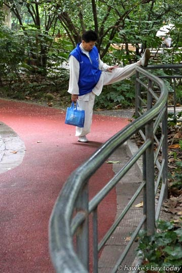 Old person stretches in a public park photograph