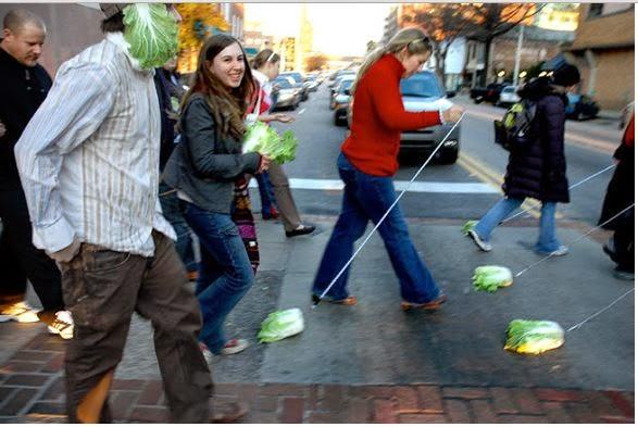 gente caminado con lechugas como si fueran perritos