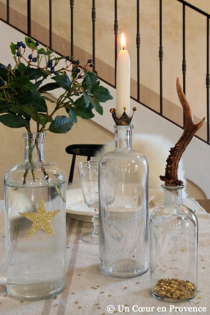 Flacons et bouteilles en verre décorés d'étoiles dorées décorent un centre de table pour les fêtes de Noël