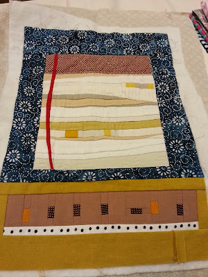 a miniture modern art quilt with a blue border