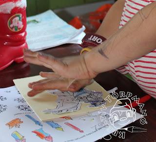 Szöveg: ... vagy kollázstechnikát felhasználó képeslap. Kép: Közelkép ugyanaz a jobbkézen sportórát hordó gyerekkezecske tulajdonosáról, amint két kézzel nyomja a kivágott figurákat a kartonpapírhoz.