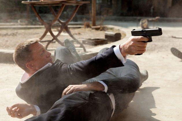 Daniel Craig as James Bond aiming a gun in Skyfall movieloversreviews.blogspot.com