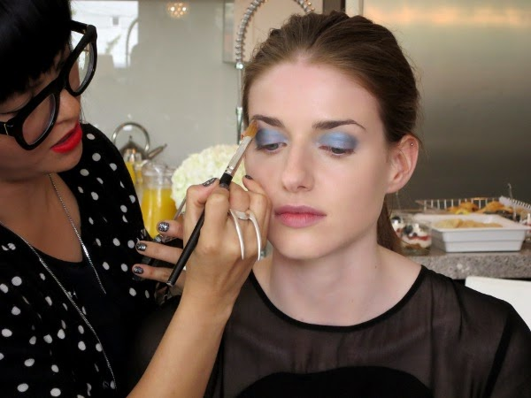 CoverGirl makeup artist Veronica Chu applies blue eyeshadow to the model's eyelids.