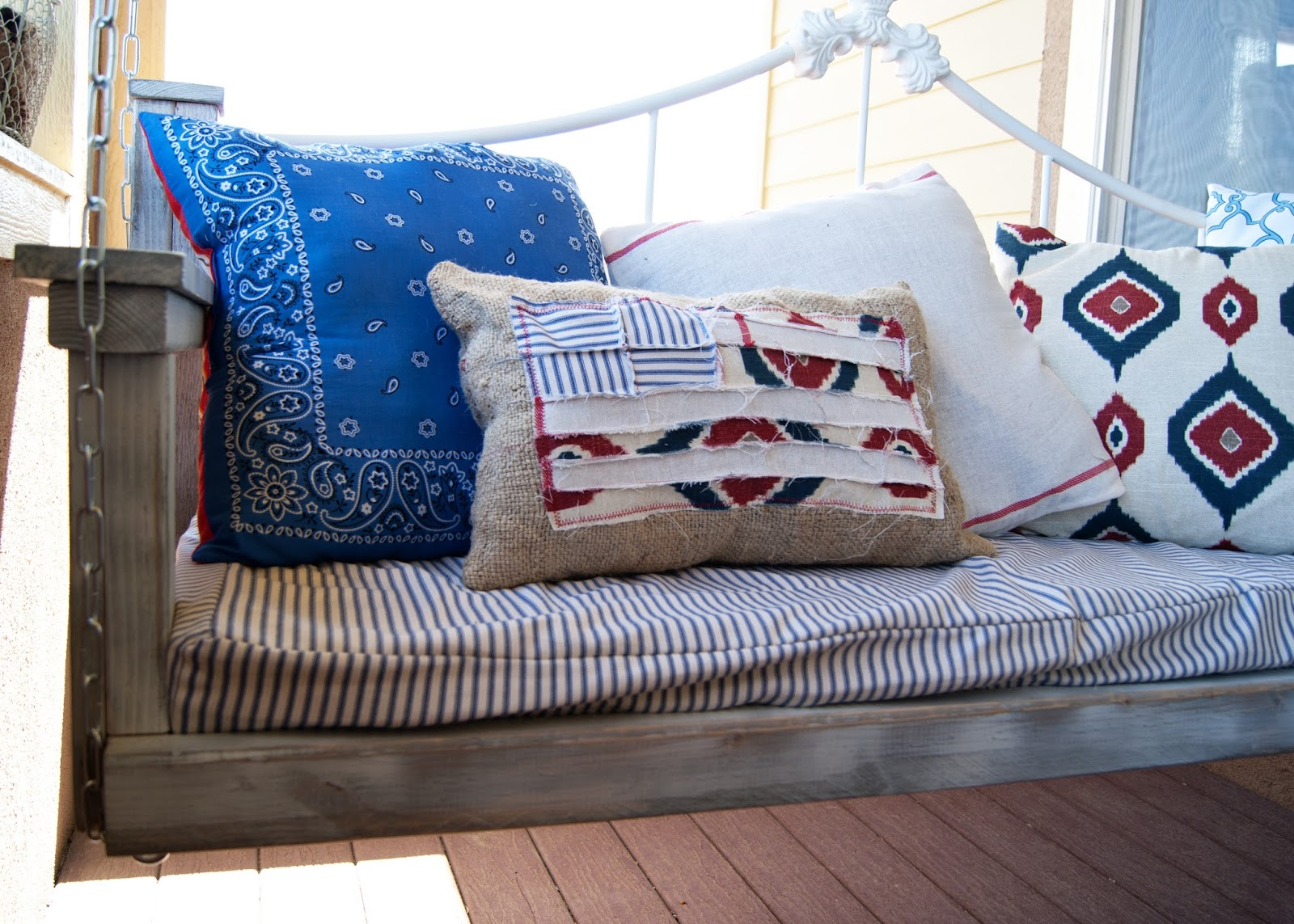 Scrappy Flag Pillow on porch swing