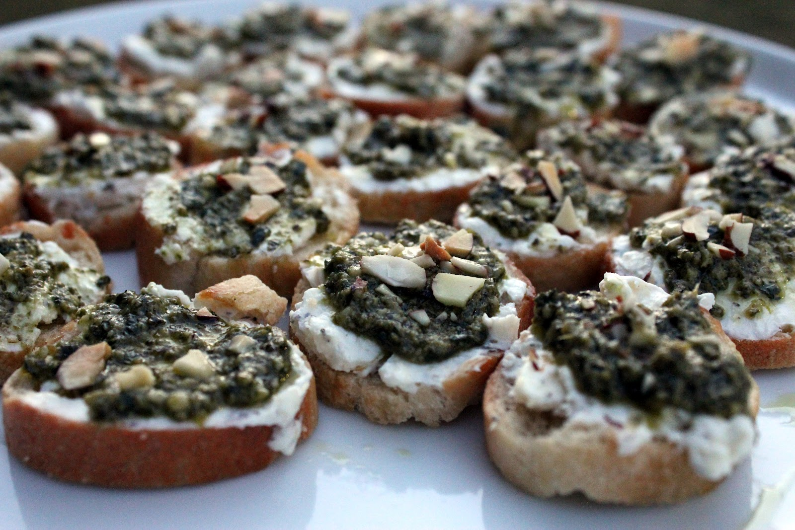 She showed up with these Goat Cheese Pesto Crostini and within minutes ...