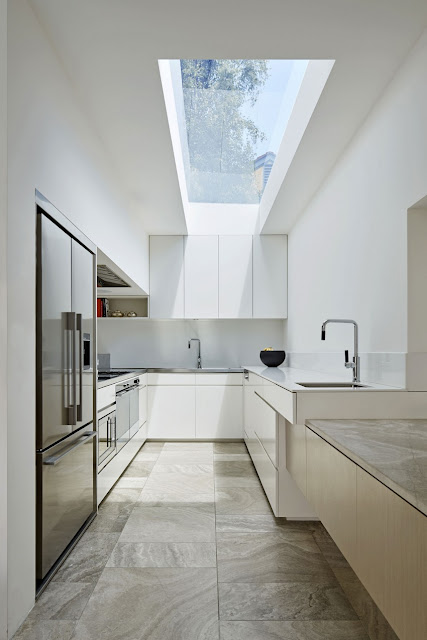Small modern kitchen in white color, stone flooring, natural light through out the glass roofing.