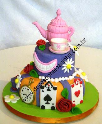 Bolo decorado bule e xícara no topo do bolo e decorações baseadas no tema:  o sorriso do Gato Risonho, a cartola do Chapeleiro Louco, o relógio da Lebre Maluca, e as cartas de baralho que pintam as rosas de vermelho no jardim da Rainha de Copas.