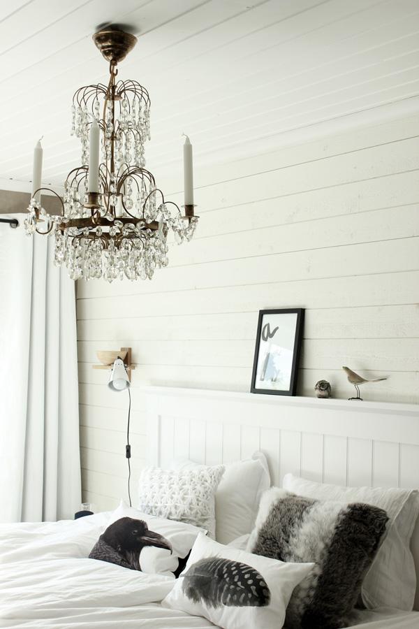 sovrum i svart och vitt, kristallampa i sovrummet, kuddar i svart och vitt, sovrum med panel som fondvägg, vitt och svart