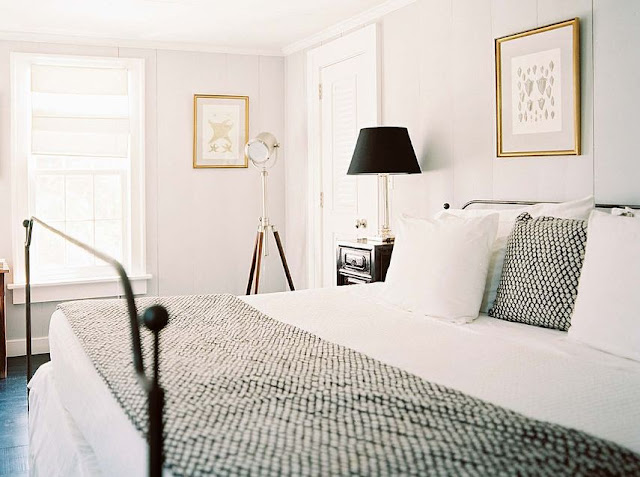 White bedroom with paneled walls, a dark wood floor, iron bed frame, black pillow with white poka dots and a matching throw pillow at the foot of the bed. The black nightstand has a tall brass lamp with a black lampshade