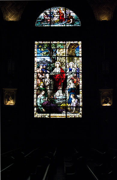 Brilliant stained glass window depicting Jesus healing the sick against a dark church background