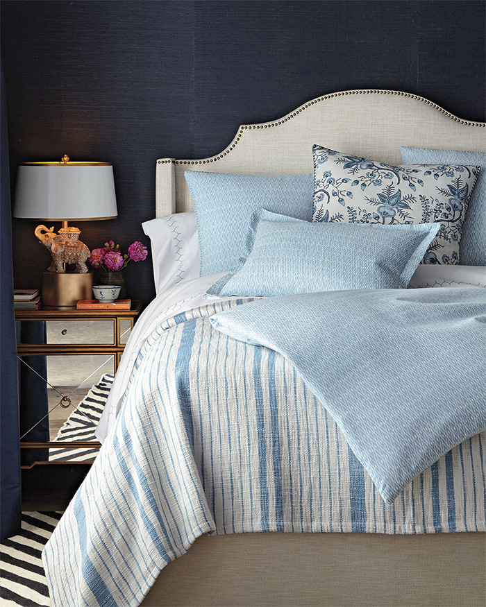 John Robshaw uses blue and white stripes plus patterns combine to create this fantastic bedding.
