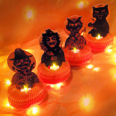 Scarecrow, witch, devil, and black cat hold little battery-operated tealights in this holiday display by product-artist Bindlegrim.