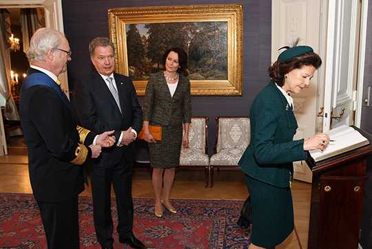 Queen Silvia and King Carl XVI Gustaf of Sweden sign the guestbook during their visit to Finnish Parliament in Helsinki, hosted by speaker of Finnish Parliament Eero Heinaluoma