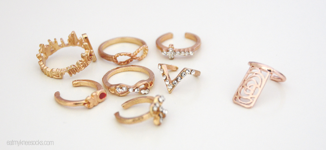 The 7 piece golden ring set and floral cutout nail ring from Born Pretty Store, laid out.