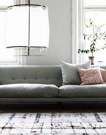 lækker styling af stue med gulvtæppe, grå sofa og let og enkel lampe