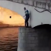 What triggers this man to climb down from a bridge?