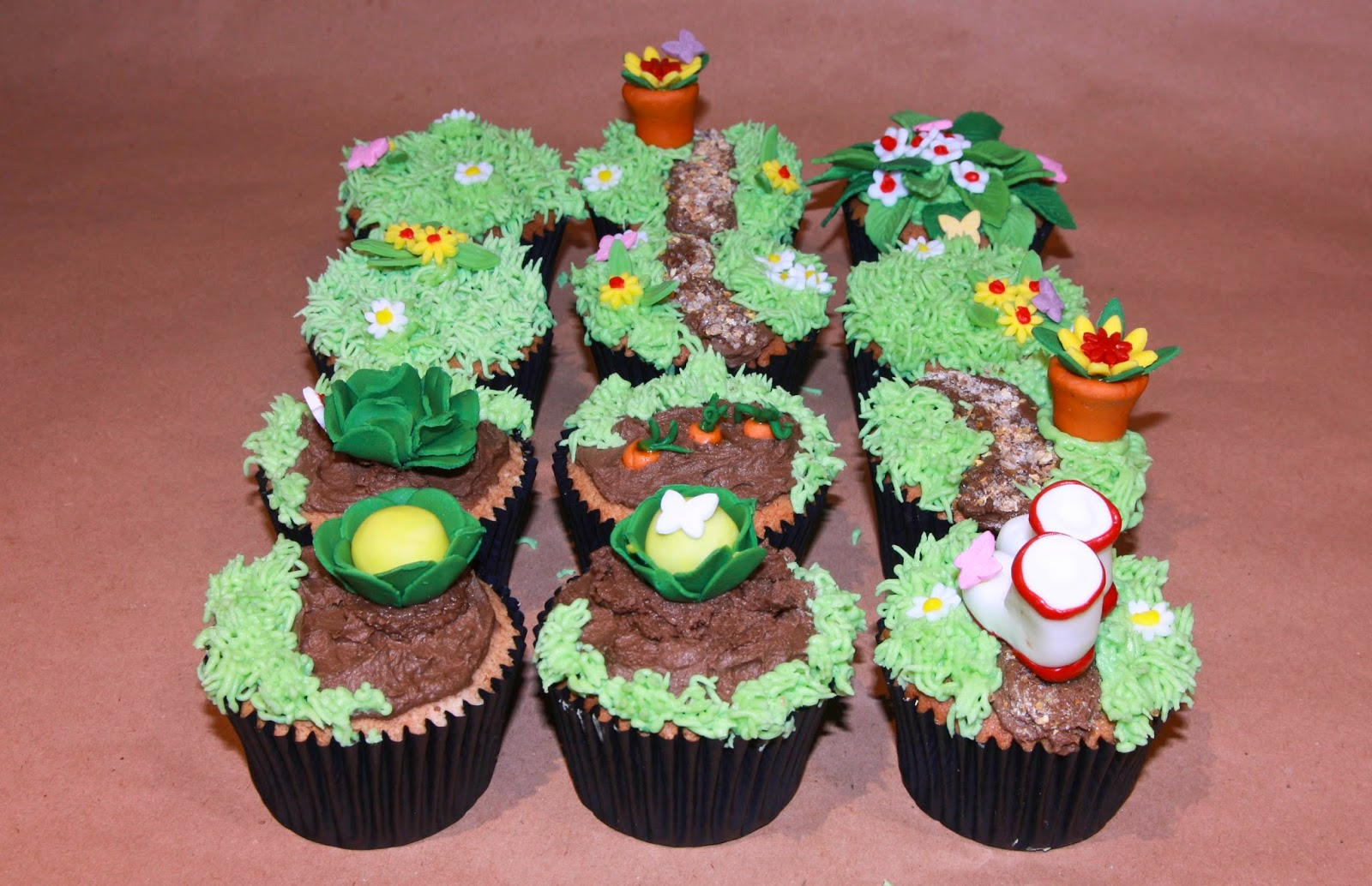 12 Earl Grey cupcakes topped with lemon buttercream and decorated with a garden theme